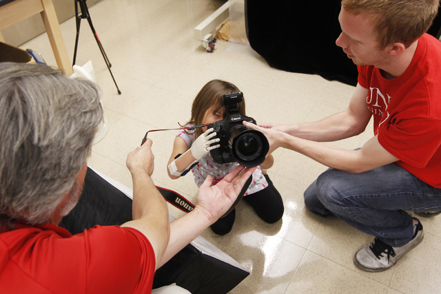 Hailey Dawson uses her new prosthetic hand to take a photo with UNLV Photo Services photographer Aaron Mayes' camera Thursday, Oct. 30, 2014 at UNLV. (Sam Morris/Las Vegas Review-Journal)