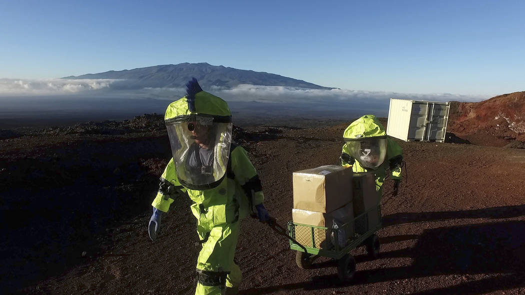 In this 2017 photo released by the University of Hawaii crew members of Mission V, walk up hill with a cart next to the university's facility Hawaii Space Exploration Analog and Simulation (HI-S ...