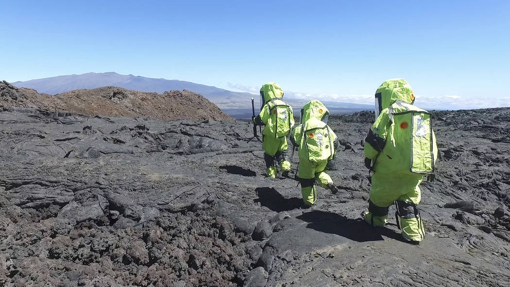 In this 2017 photo released by the University of Hawaii crew members of Mission V, walk across lava next to the university's facility Hawaii Space Exploration Analog and Simulation (HI-SEAS) at  ...