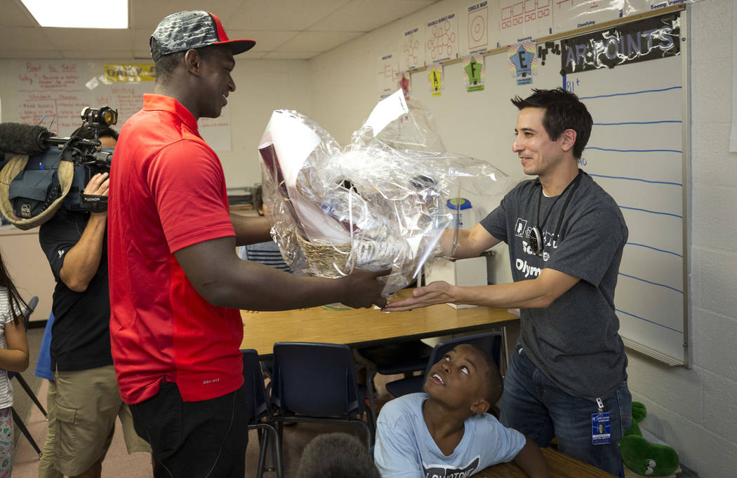 UNLV football player Jalil Briley, left, hands a gift basket to his former math teacher Christopher Ho during a surprise visit to his old grade school at Mabel Hoggard Elementary School in Las Veg ...