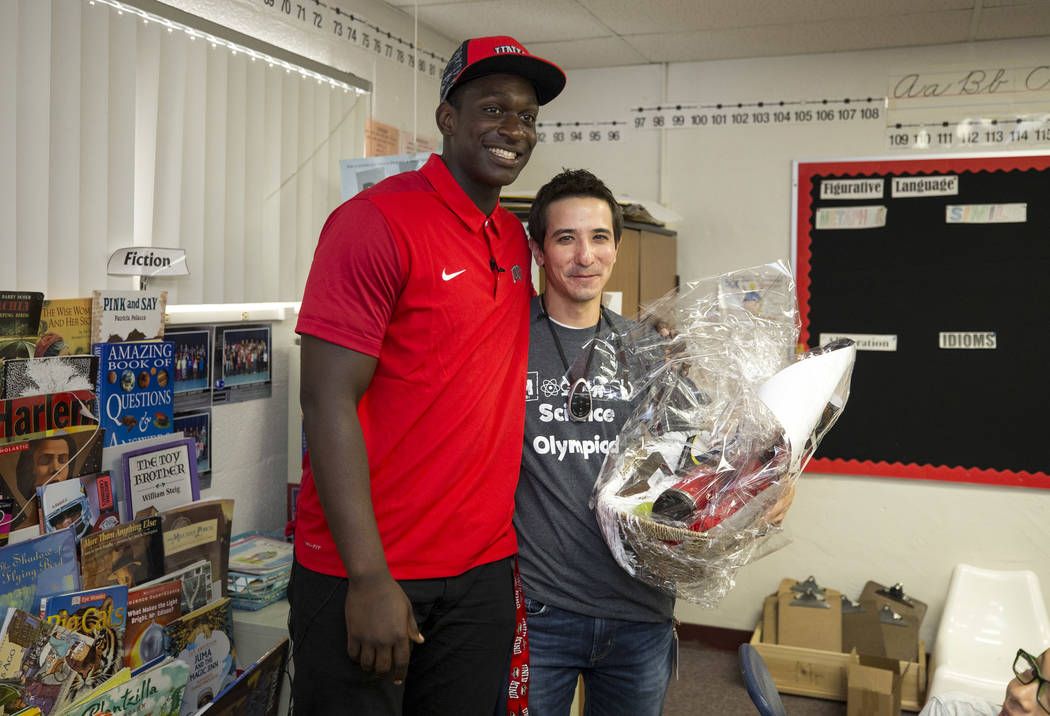 UNLV football player Jalil Briley, left, with his former math teacher Christopher Ho after a surprise visit to his old grade school at Mabel Hoggard Elementary School in Las Vegas on Friday, Sept. ...