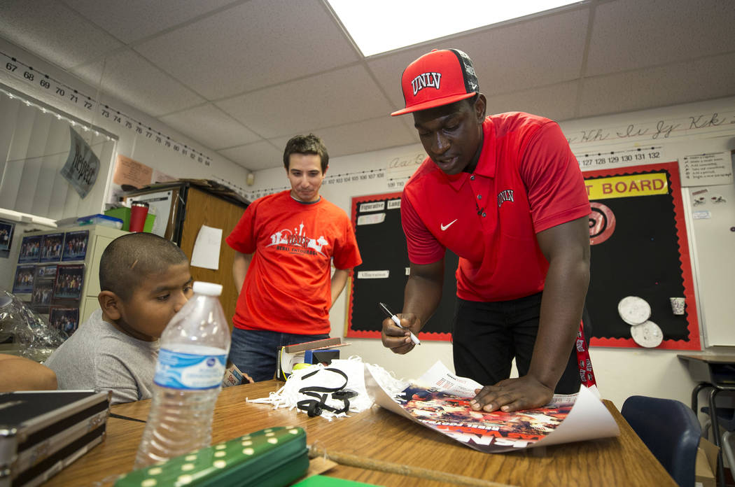 UNLV football player Jalil Briley, right, autographs a poster for his his former math teacher Christopher Ho during a surprise visit to his old grade school at Mabel Hoggard Elementary School in L ...