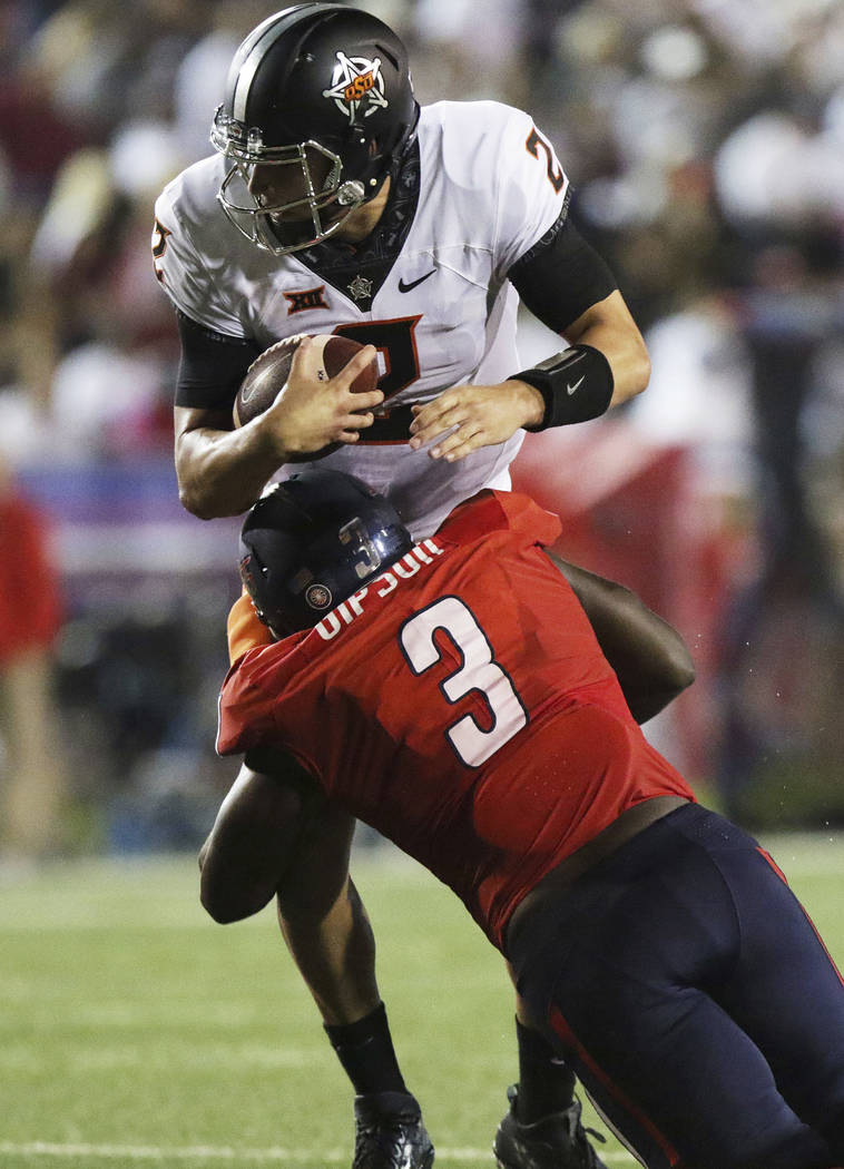Oklahoma State quarterback Mason Rudolph, top, is tackled by South Alabama defensive end Jimmie Gipson during the first half of an NCAA college football game, Friday, Sept. 8, 2017, in Mobile, Ala ...