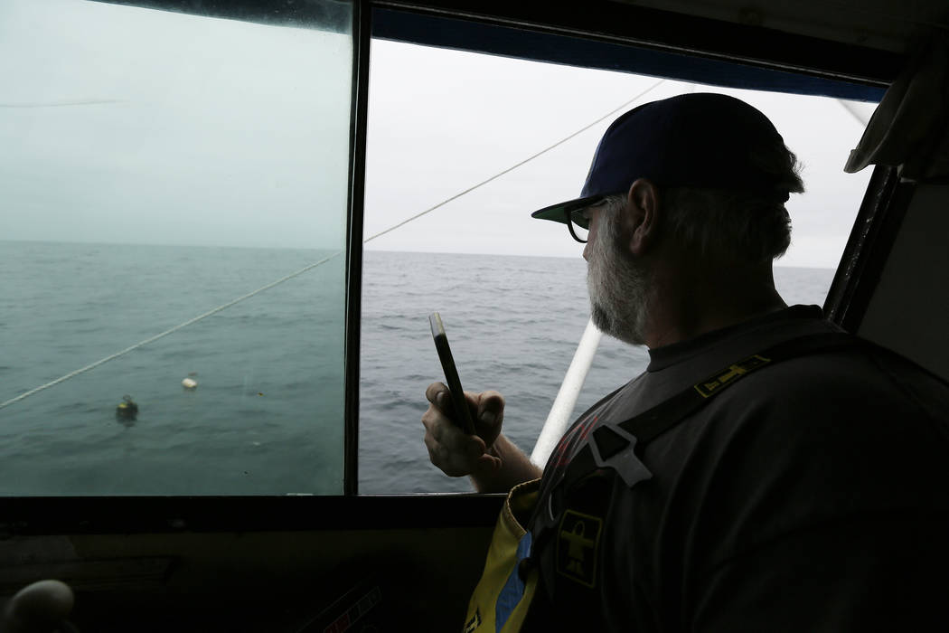 Jake Bunch uses his phone to mark the position of an abandoned crab pot off Half Moon Bay, Calif., last month. (AP Photo/Eric Risberg)