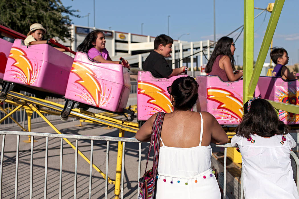 Alma Escamilla, left, and her daughter Valentina, 9, right, watch as her son Cristiano, 4, top left, rides a rollercoaster during a Mexican Independence Day celebration in North Las Vegas, Saturda ...