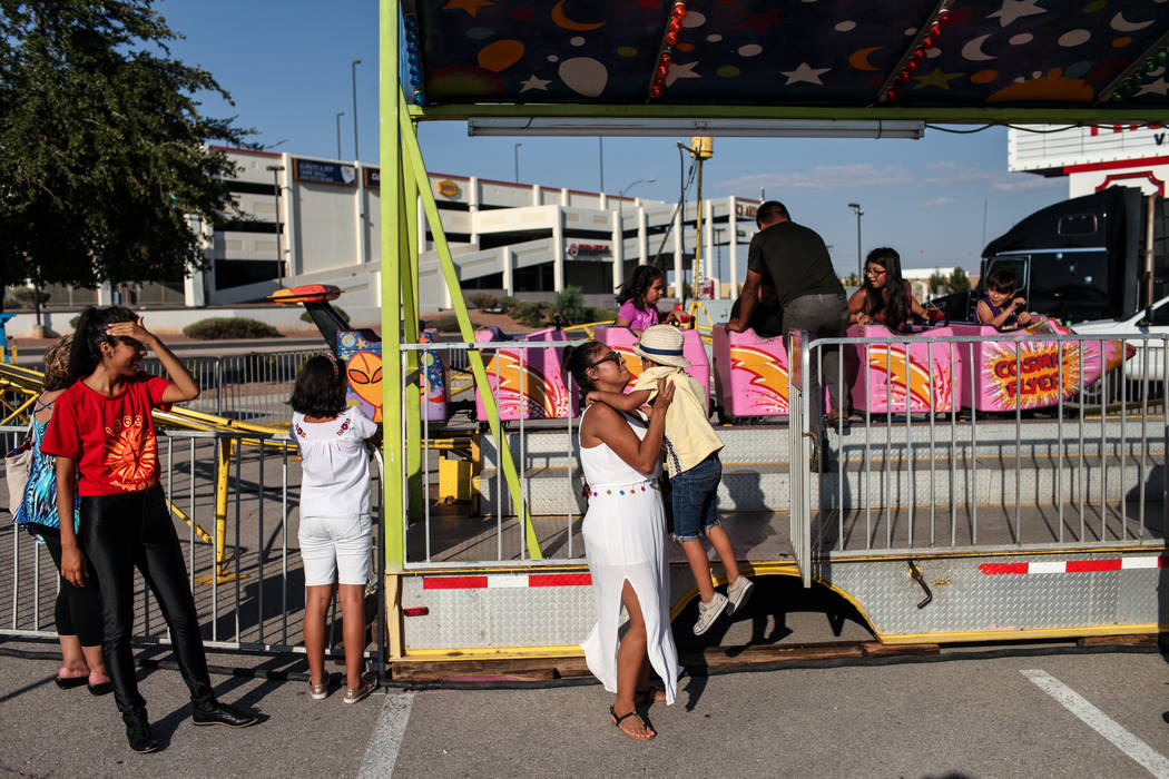 Alma Escamilla, left, lifts her son Cristiano, 4, right, after riding a rollercoaster during a Mexican Independence Day celebration in North Las Vegas, Saturday, Sept. 16, 2017. Joel Angel Juarez  ...