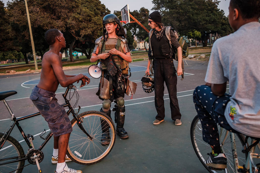 John Cookenboo, left, and Vincent Yochelson take a minute to explain who they are and what they are about, and show off some of their gear to a couple of local kids at a park in Oakland. (Photo by ...
