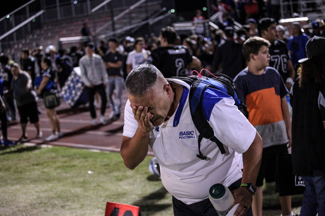 A Basic Academy coach flushes his eyes after being pepper sprayed by an officer after a brawl between Canyon Springs and Basic Academy's football teams at the end of a game at Basic Academy of Int ...