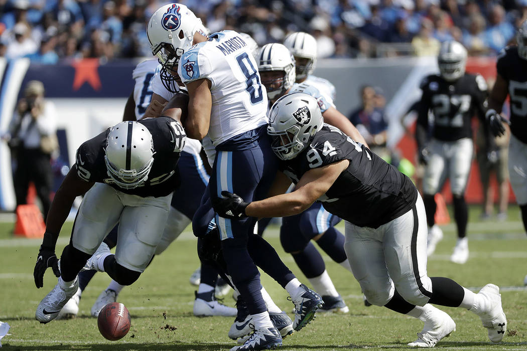 Oakland Raiders defensive end Khalil Mack (52) and defensive tackle Eddie Vanderdoes (94) chase after a fumble by Tennessee Titans quarterback Marcus Mariota (8) in the second half of an NFL footb ...