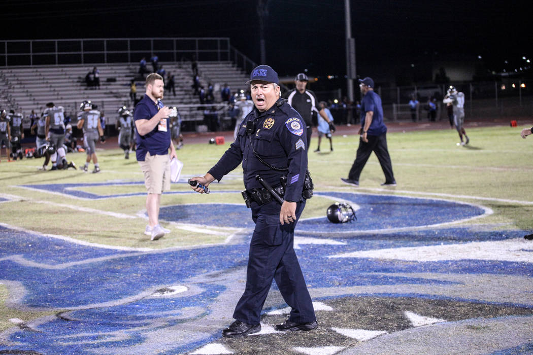 A police officer holds pepper spray after dispersing a brawl between Canyon Springs and Basic Academy's football teams at the end of a game at Basic High School in Henderson, Friday, Sept. 15, 201 ...
