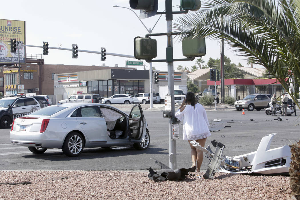 A woman sits on her phone at the site of an accident at the intersection of Decatur Boulevard and Spring Mountain Road in Las Vegas, Saturday, Sept. 16, 2017. Gabriella Angotti-Jones Las Vegas Rev ...