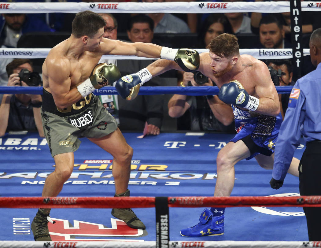 "Gennady ҇GGӠGolovkin, left, trades blows with Saul ""Canelo"" Alvarez during their middleweight championship boxing match at T-Mobile Arena in Las Vegas on Saturday, Se ..."