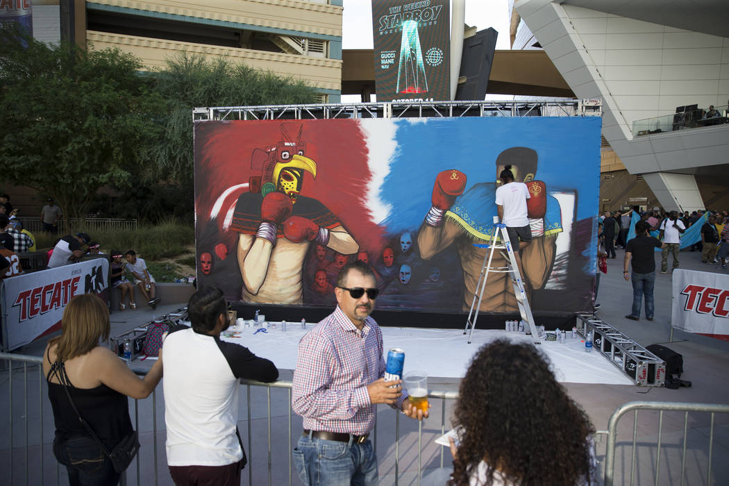 An artists paints a mural outside of T-Mobile Arena in Las Vegas where Saul Canelo Alvarez and Gennady GGG Golovkin at scheduled to fight in a championship bout, Saturday, Sept. 16, 2017. Erik Ver ...