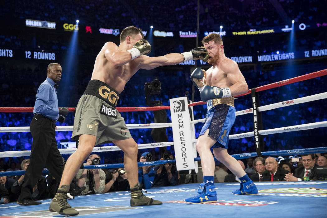 Gennady GGG Golovkin, left, connects a punch against Saul Canelo Alvarez in the WBC, WBA, IBF, RING middleweight title bout at T-Mobile Arena in Las Vegas, Saturday, Sept. 16, 2017. The fight ende ...