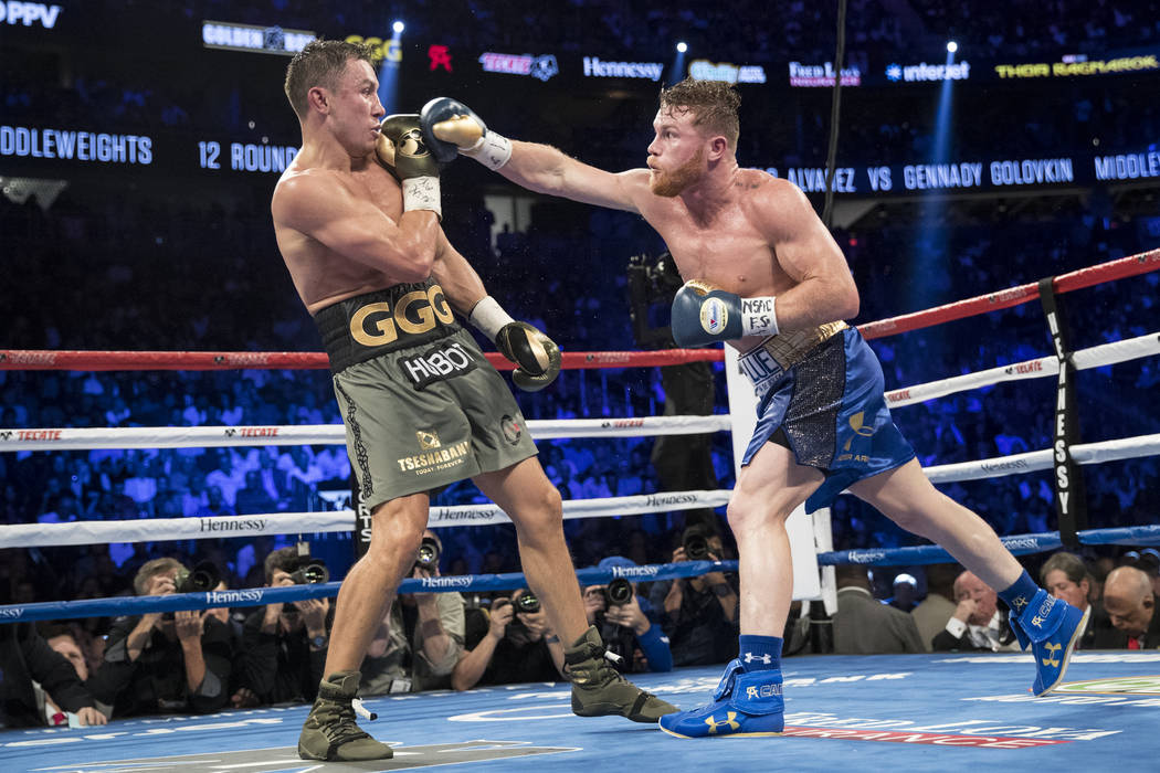 Saul Canelo Alvarez, right throws a punch against Gennady GGG Golovkin in the WBC, WBA, IBF, RING middleweight title bout at T-Mobile Arena in Las Vegas, Saturday, Sept. 16, 2017. The fight ended  ...