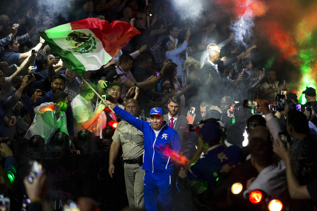 A team member of Saul Canelo Alvarez waves a flag as Alvarez makes his way to the ring for his fight against Gennady GGG Golovkin in the WBC, WBA, IBF, RING middleweight title bout at T-Mobile Are ...