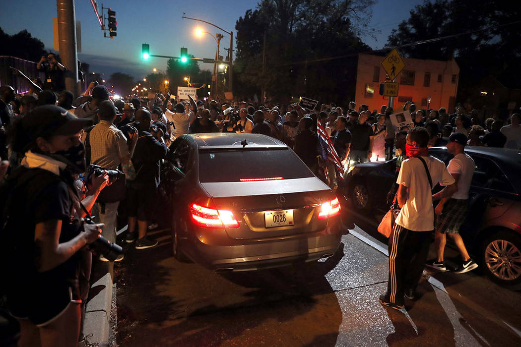 Protesters surround a car as they march in the street response to a not guilty verdict in the trial of former St. Louis police officer Jason Stockley Saturday, Sept. 16, 2017, in St. Louis.  (AP P ...