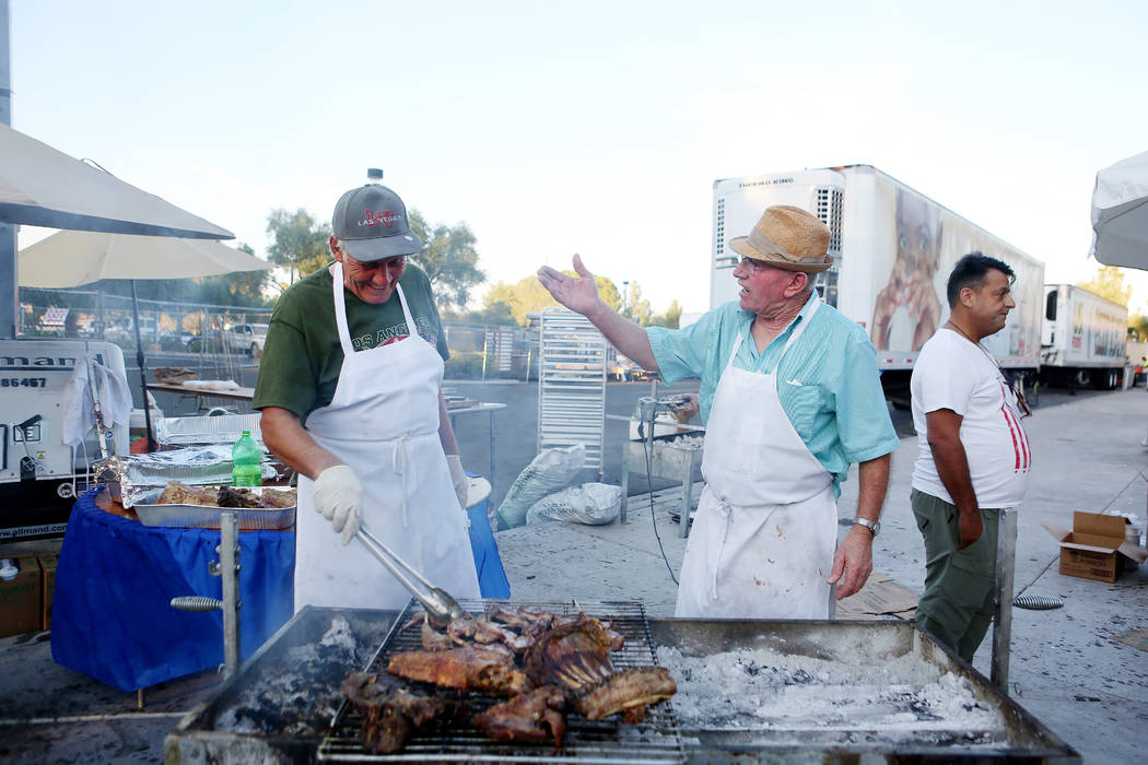 Members of St. John the Baptist Greek Orthodox Church John Ziogas, left, and Bobby Taxopoulos joke while cooking lamb to fundraise for the church during the during the 45th annual Greek Food Fest  ...