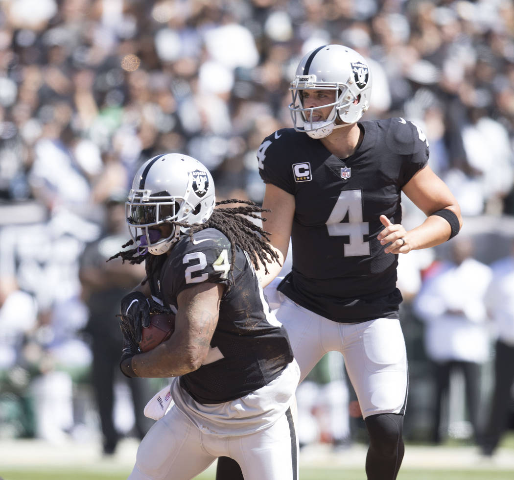 Oakland Raiders quarterback Derek Carr (4) hands off the football to running back Marshawn Lynch (24) in the first half of their game against the New York Jets in Oakland, Calif., Sunday, Sept. 17 ...