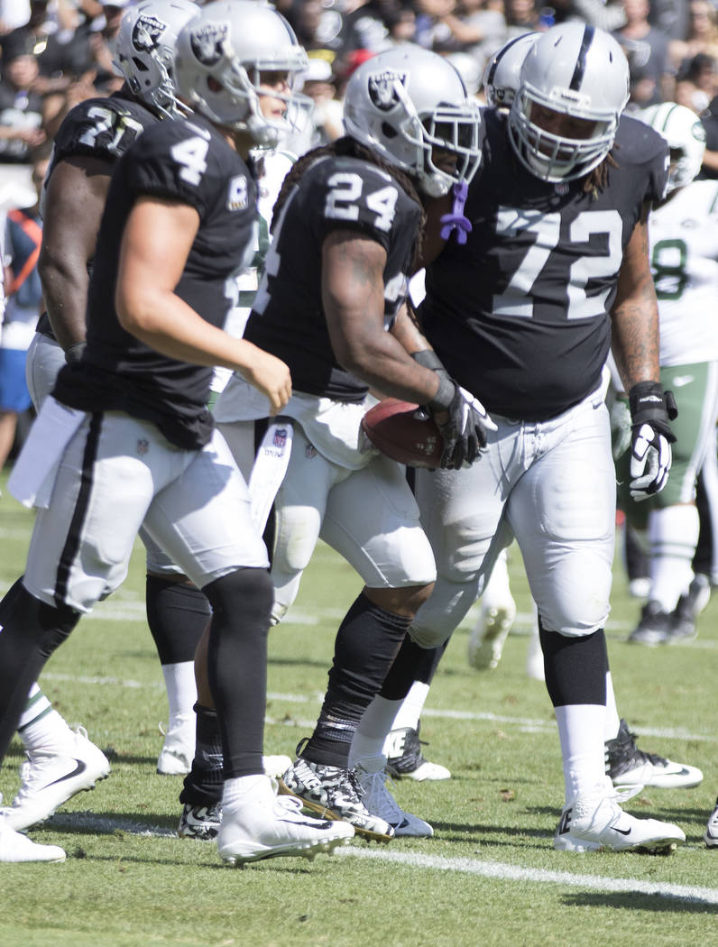 Oakland Raiders running back Marshawn Lynch (24) with quarterback Derek Carr (4) and offensive tackle Donald Penn (72) after scoring in the first half of their game in Oakland, Calif., Sunday, Sep ...