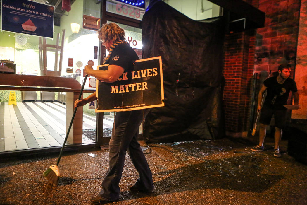 A shopkeeper cleans up glass after windows were shattered by protesters during the second night of demonstrations Sept. 16, 2017, after a not-guilty verdict in the murder trial of former St. Louis ...