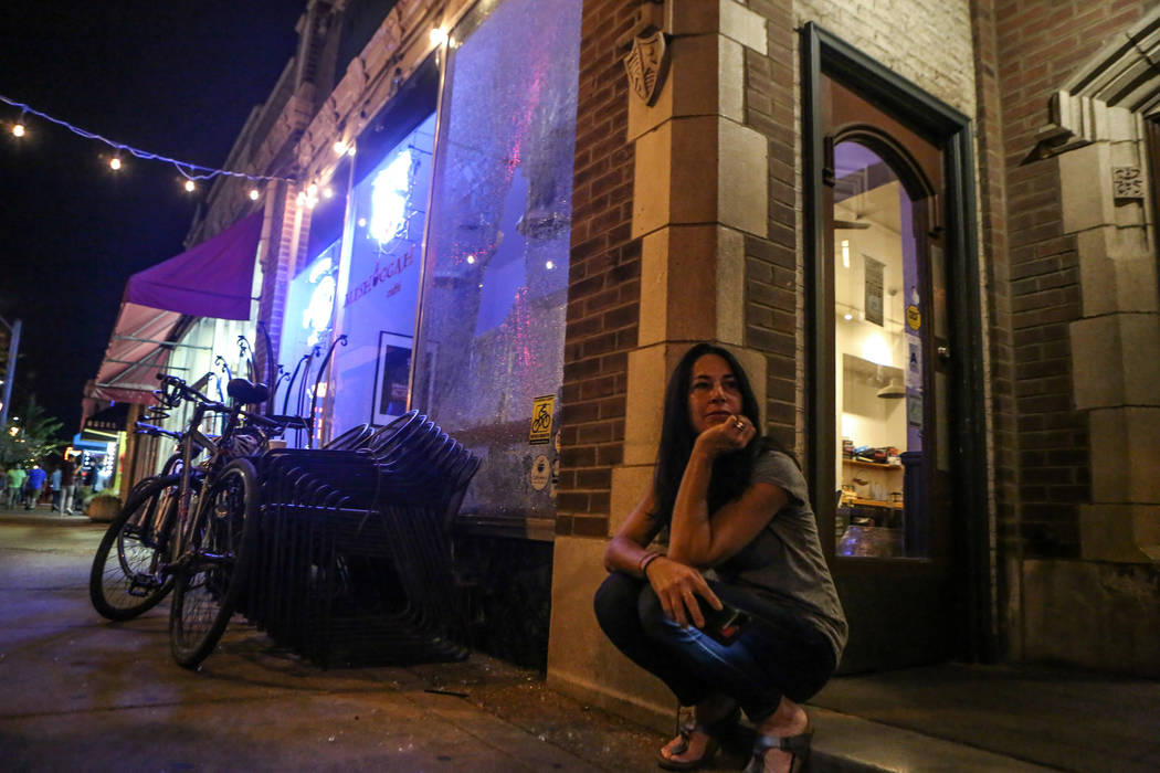 A store owner sits outside her shop Sept. 16, 2017, after her front window was shattered by protesters during the second night of demonstrations after a not guilty verdict in the murder trial of f ...