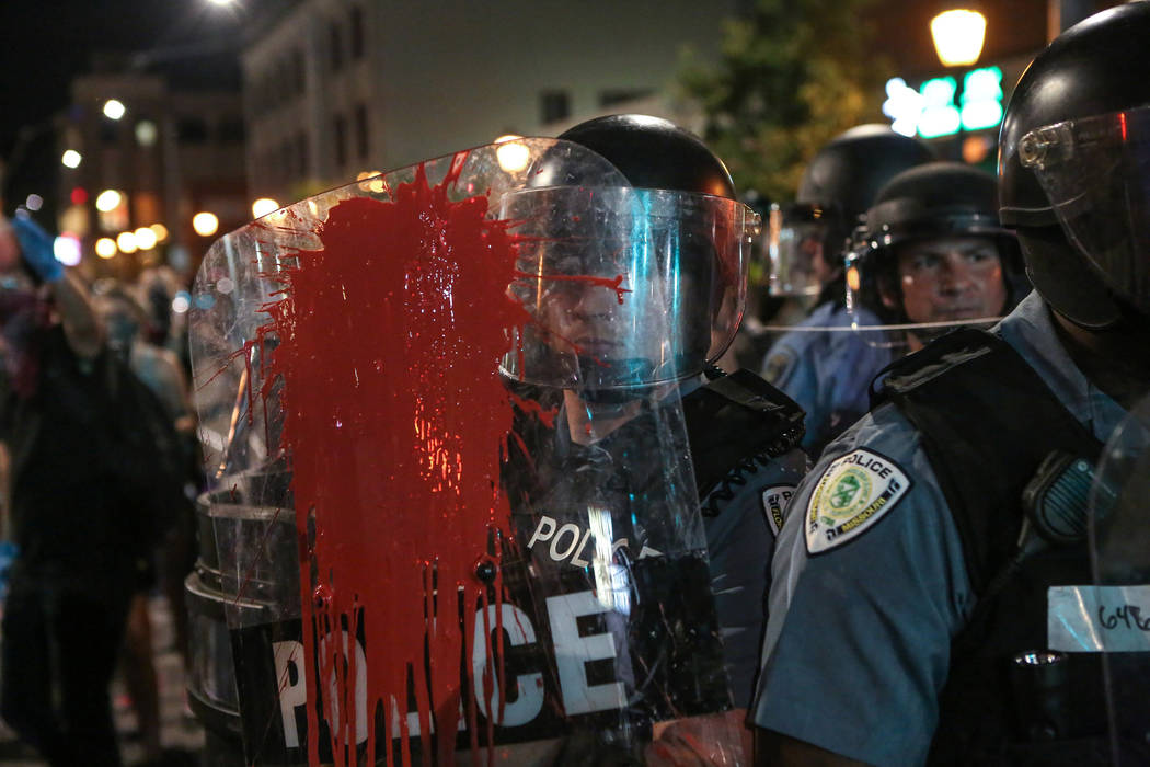 Red paint is splattered on the shield of a policeman Sept. 16, 2017, during the second night of demonstrations after a not-guilty verdict in the murder trial of former St. Louis police officer Jas ...