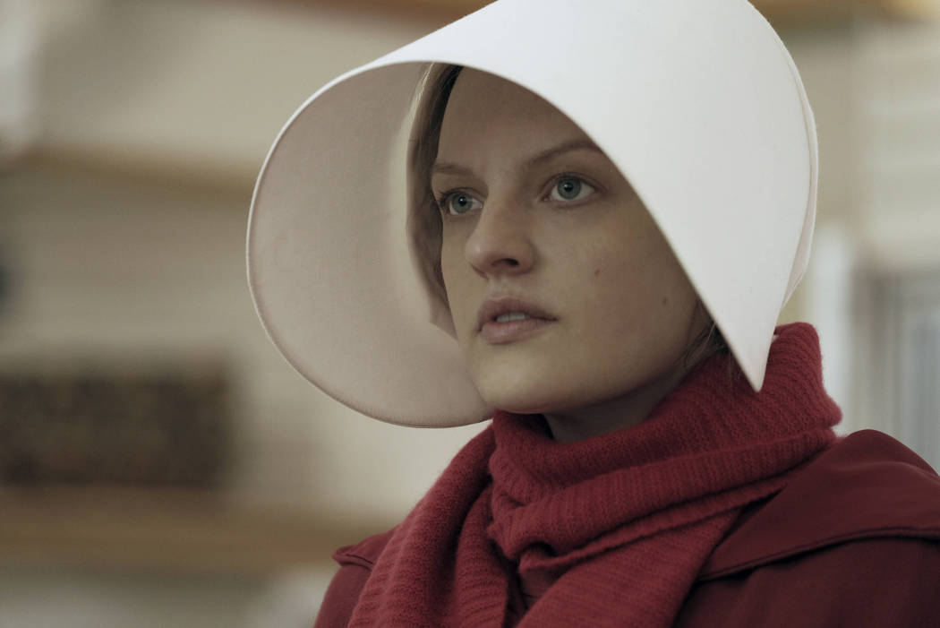 "This image released by Hulu shows Elisabeth Moss as Offred in a scene from, ""The Handmaid's Tale."" Moss is nominated for an Emmy Award for outstanding lead actress in a drama ser ..."