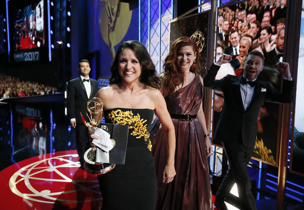 "Julia Louis-Dreyfus, winner of the award for outstanding lead actress in a comedy series for ""Veep"", left, walks on the red carpet stage with Debra Messing and Chris Hardwick at  ..."