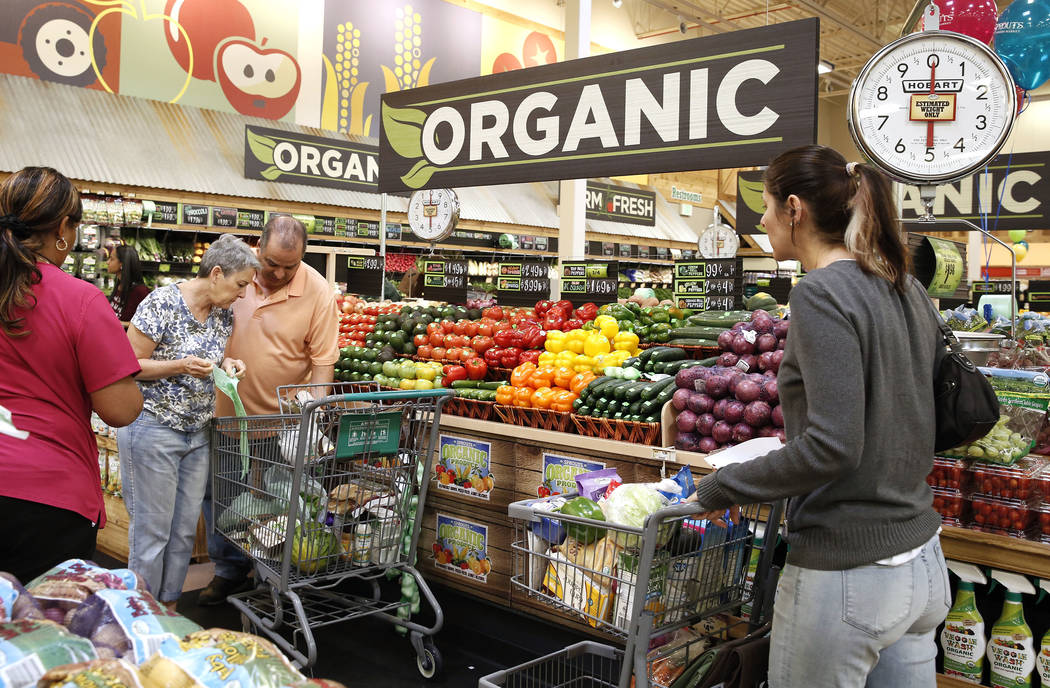Alyssa Pattinson, right, pushes a cart while shopping with her parents Alexis McConnell, second left, and Martin on the opening day of Sprouts Farmers Market on 8441 Farm Rd., in Las Vegas on Wedn ...