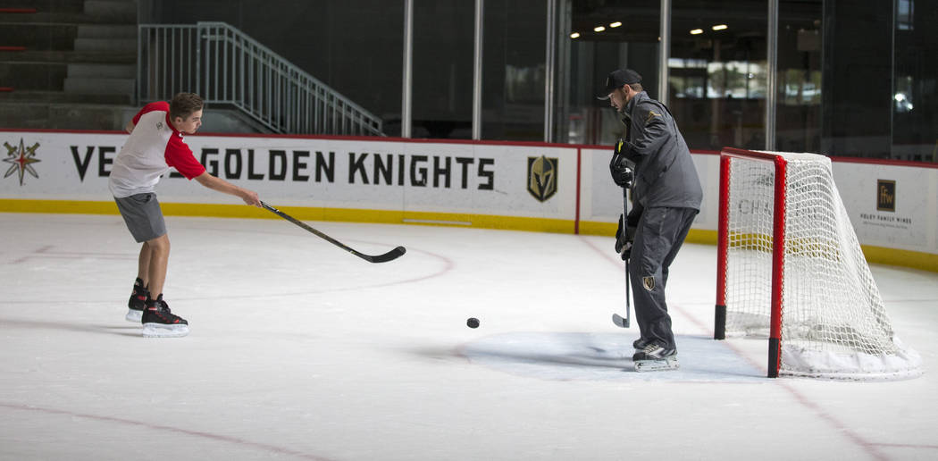 NASCAR Camping World Truck Series driver Noah Gragson, left, takes a shot on Vegas Golden Knights TV analyst Shane Hnidy during an ice hockey skills clinic at the City National Arena on Friday, Se ...