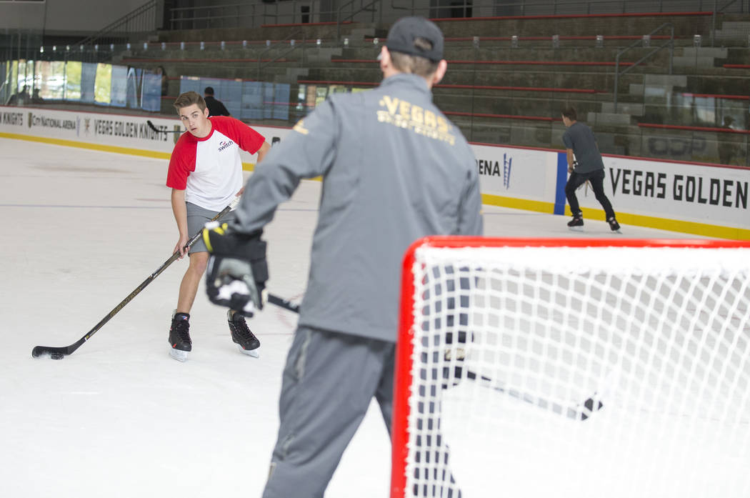 NASCAR Camping World Truck Series drivers Noah Gragson, left, takes a shot on Vegas Golden Knights TV analyst Shane Hnidy during an ice hockey skills clinic at the City National Arena on Friday, S ...