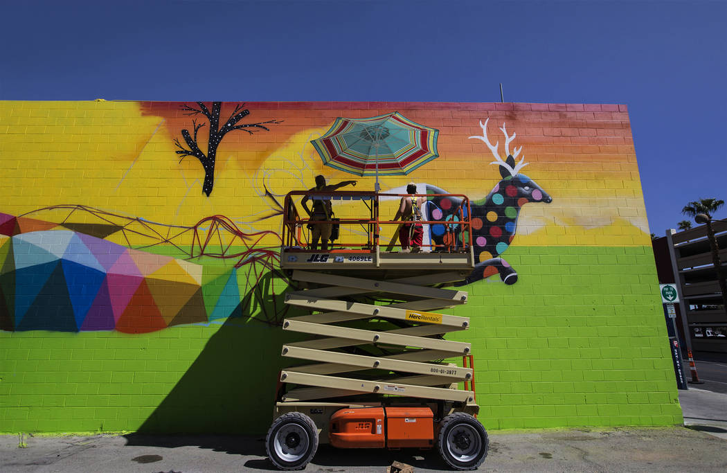 Artist Okuda San Miguel, left, works on a mural outside the Meow Wolf art motel on Monday, September 18, 2017, in Las Vegas. Benjamin Hager Las Vegas Review-Journal @benjaminhphoto