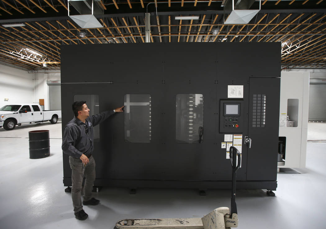 Battle Arms Development President George Huang with an Okuma horizontal computer-controlled cutting machine, which allows for faster parts production, at the new location for Battle Arms Developme ...
