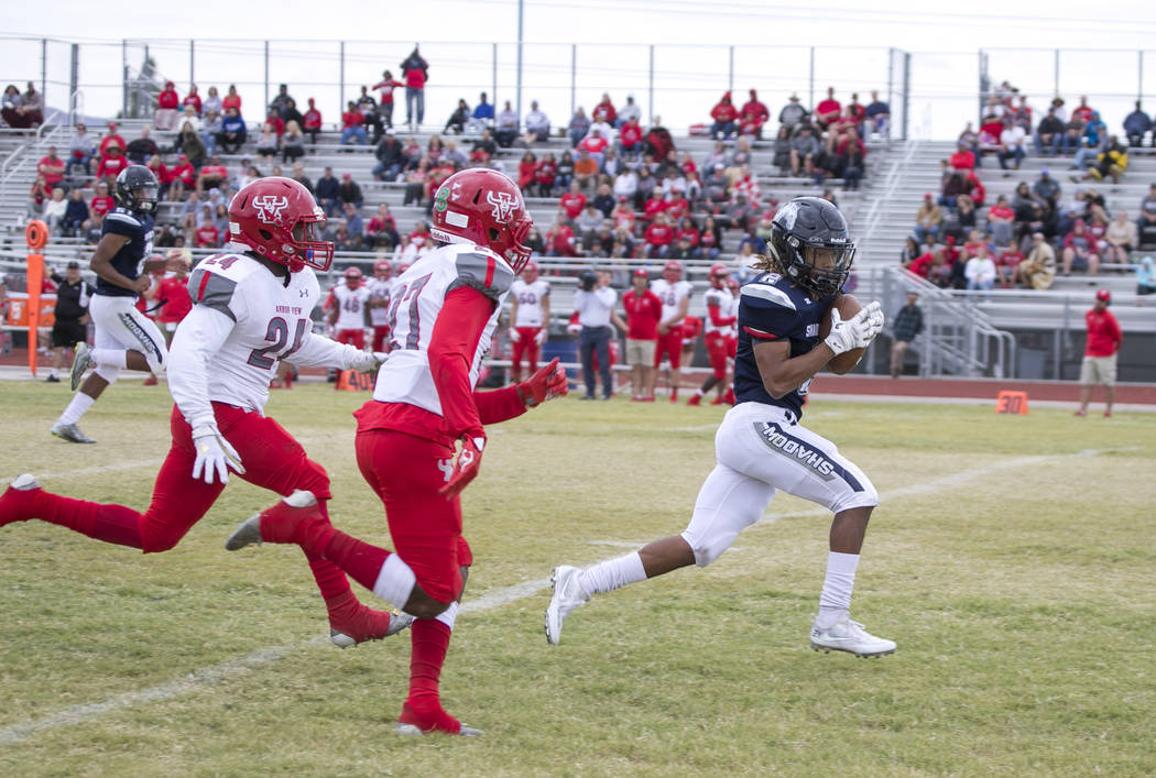 Shadow Ridge's Elisha Young (2) breaks away for a touchdown from Arbor View's Niles Scafati Boyce (27) and Rodney Pitts (24) during a football game at Shadow Ridge High School on Saturday, Sept. 2 ...