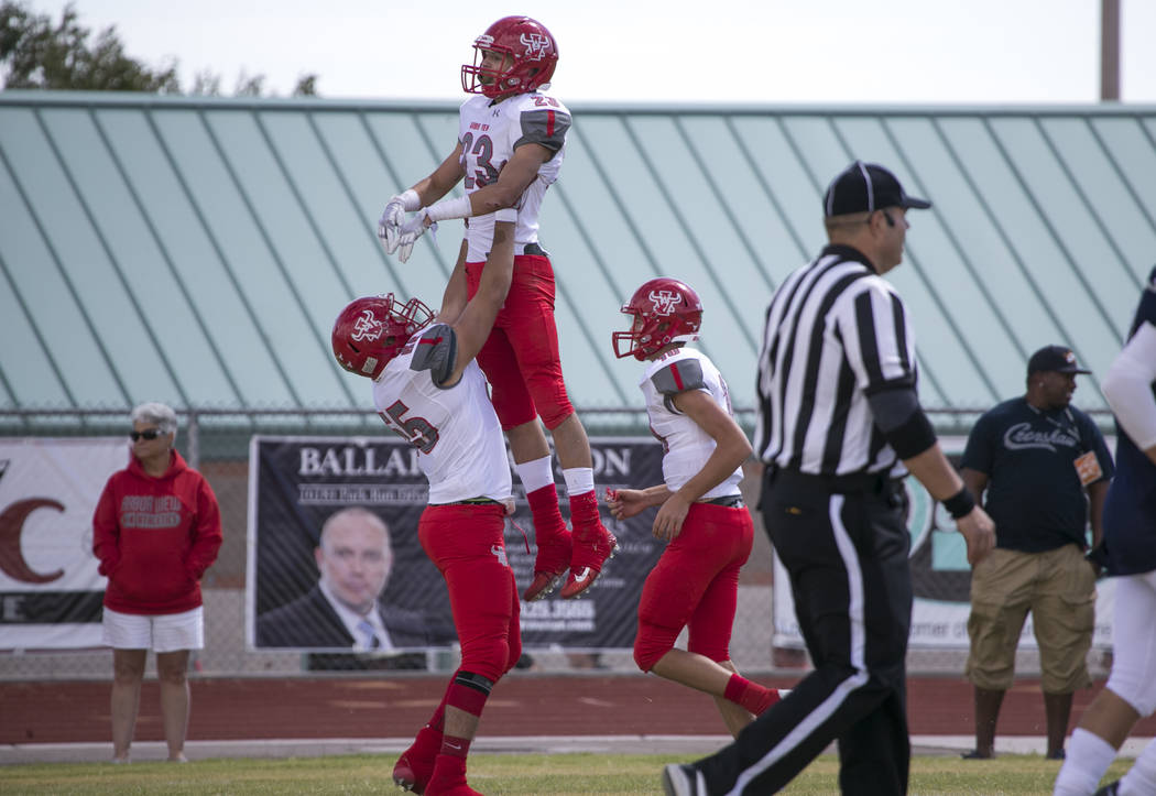 Arbor View's Deago Stubbs (23) is lifted up by Cristian Taylor (55) after scoring a touchdown against Shadow Ridge during a football game at Shadow Ridge High School on Saturday, Sept. 23, 2017, i ...