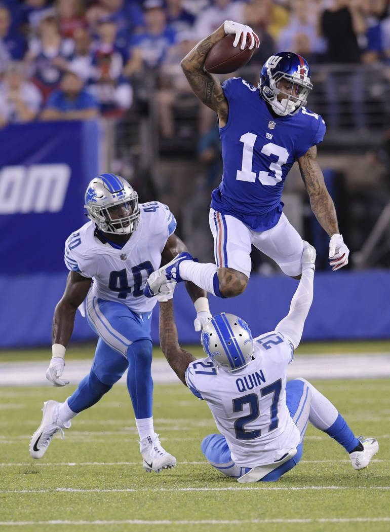 New York Giants wide receiver Odell Beckham (13) leaps over Detroit Lions' Glover Quin (27) as Jarrad Davis (40) watches during the first half of an NFL football game, Monday, Sept. 18, 2017, in E ...