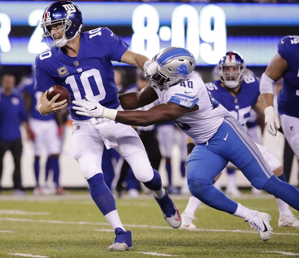 New York Giants quarterback Eli Manning (10) is sacked by Detroit Lions' Jarrad Davis (40) during the first half of an NFL football game, Monday, Sept. 18, 2017, in East Rutherford, N.J. (AP Photo ...