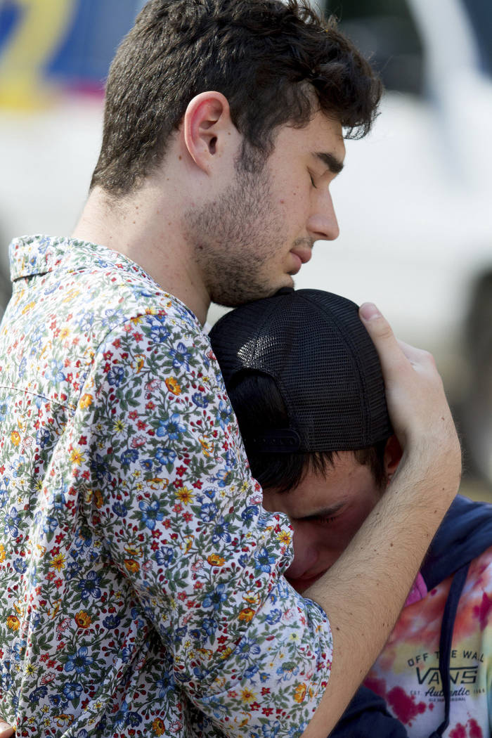 In this photo taken Sept. 17, 2017, mourners hug at a memorial for Georgia Tech student Scout Schultz in Atlanta, Ga. Schultz was a 21-year-old who was shot and killed during a confrontation with  ...