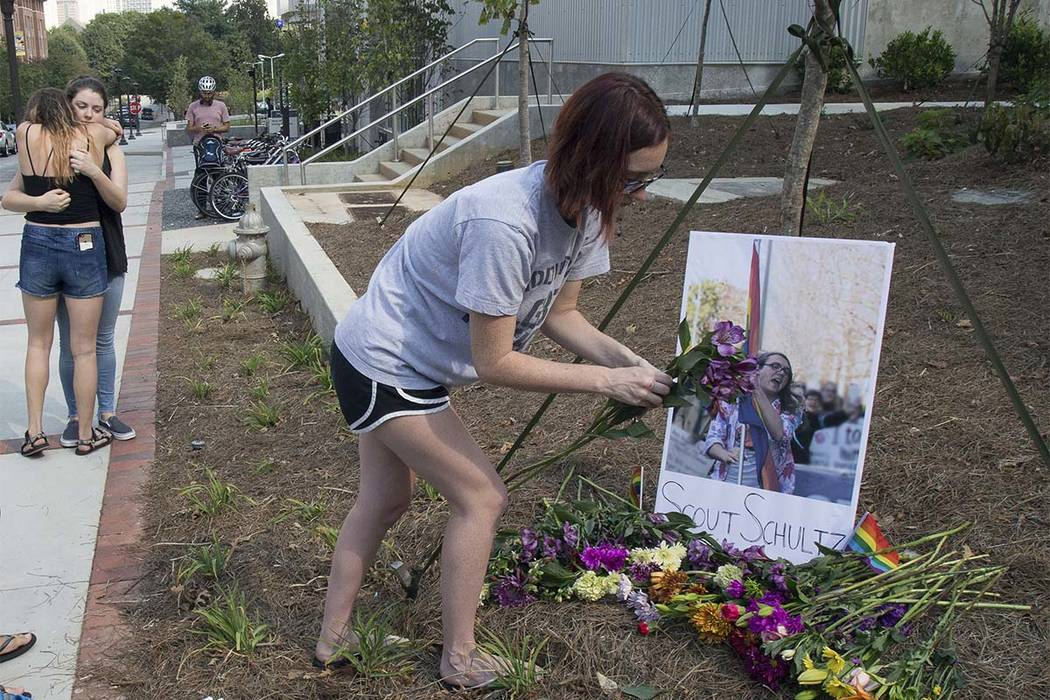 In this photo taken Sept. 17, 2017, a mourner sets out flowers at a memorial for Georgia Tech student Scout Schultz in Atlanta, Ga. Schultz was a 21-year-old who was shot and killed during a confr ...