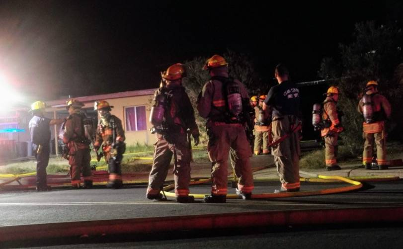 Firefighters examine the damage at 2011 E. Phillips Ave. after an early morning fire. The fire is believed to have started in the carport. (Max Michor/Las Vegas Review-Journal)