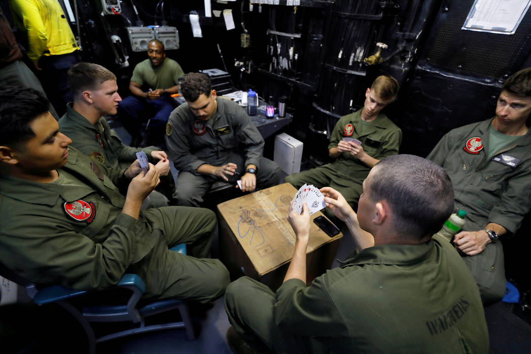 Marine Corps crew chiefs and maintenance personnel play cards in a room near the flight deck of the USS Kearsarge as the vessel handles some of the evacuation of U.S. military personnel from the U ...