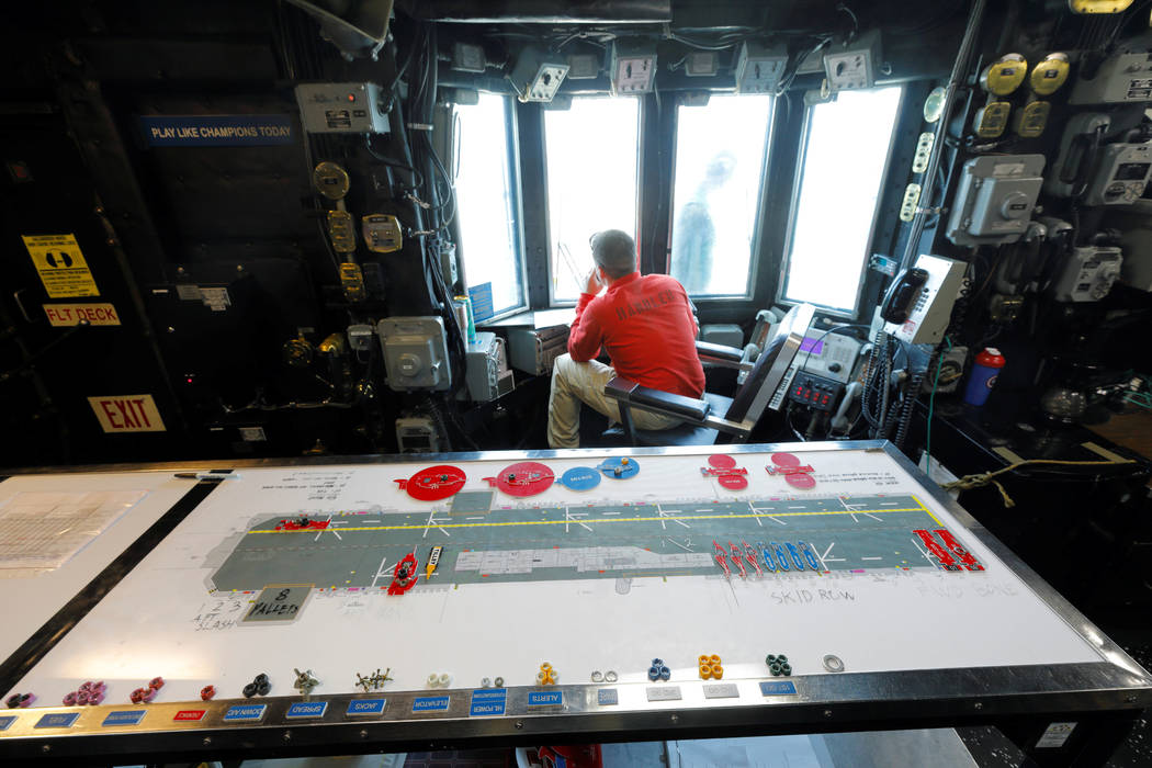 A handler works in one of the USS Kearsarge's control rooms near a live schematic of the flight deck as the vessel handles some of the evacuation of U.S. military personnel from the U.S. Virgin Is ...