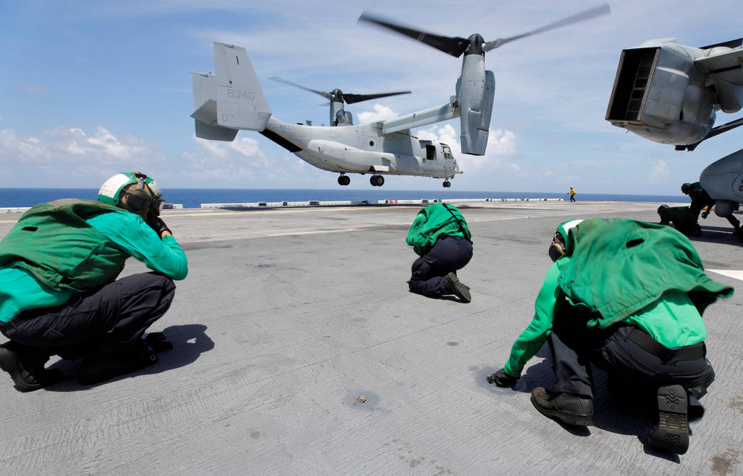 Crewmen brace themselves from the propeller wash of a Marine Corps MV-22B Osprey departing the aboard the USS Kearsarge as U.S. military continues to evacuate from the U.S. Virgin Islands in advan ...
