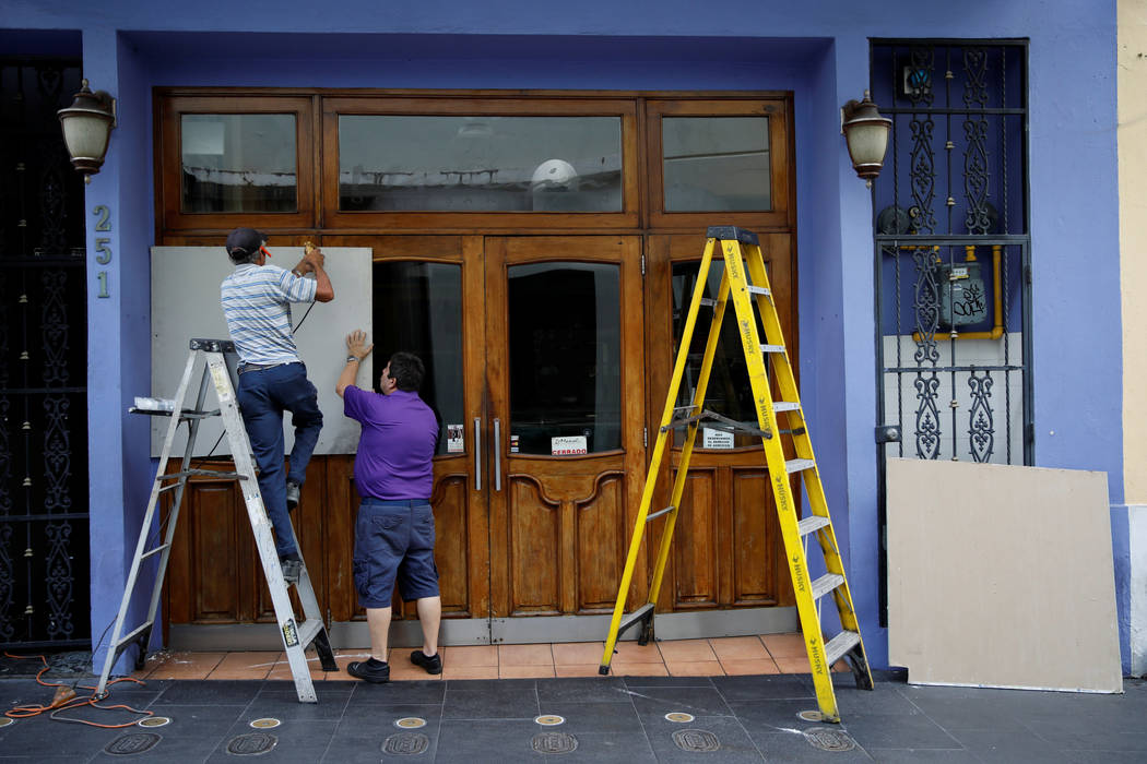 Men cover the windows of a restaurant in preparation for Hurricane Maria in San Juan, Puerto Rico September 19, 2017. (Carlos Garcia Rawlins/reuters)