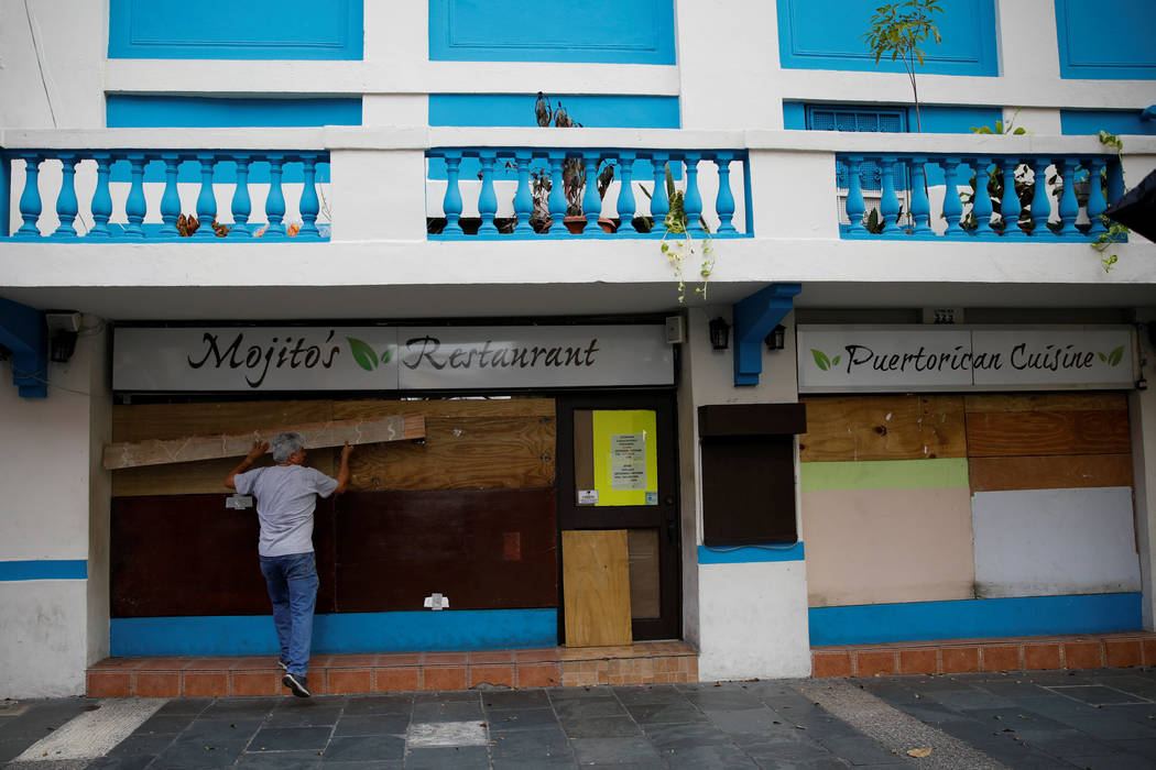 A man covers the windows of a restaurant in preparation for Hurricane Maria in San Juan, Puerto Rico September 19, 2017. (Carlos Garcia Rawlins/reuters)