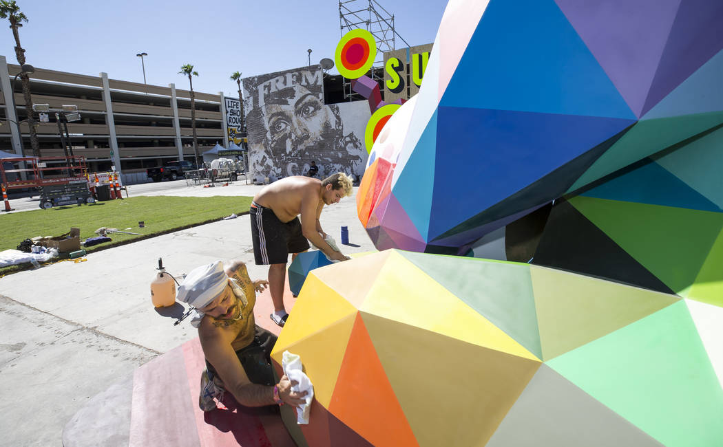 Pablo Hattori, left, and Marcos Martinez, assistants to Spanish street artist Okuda San Miguel, clean up a sculpture created by Okuda in preparation for the Life is Beautiful festival in downtown  ...