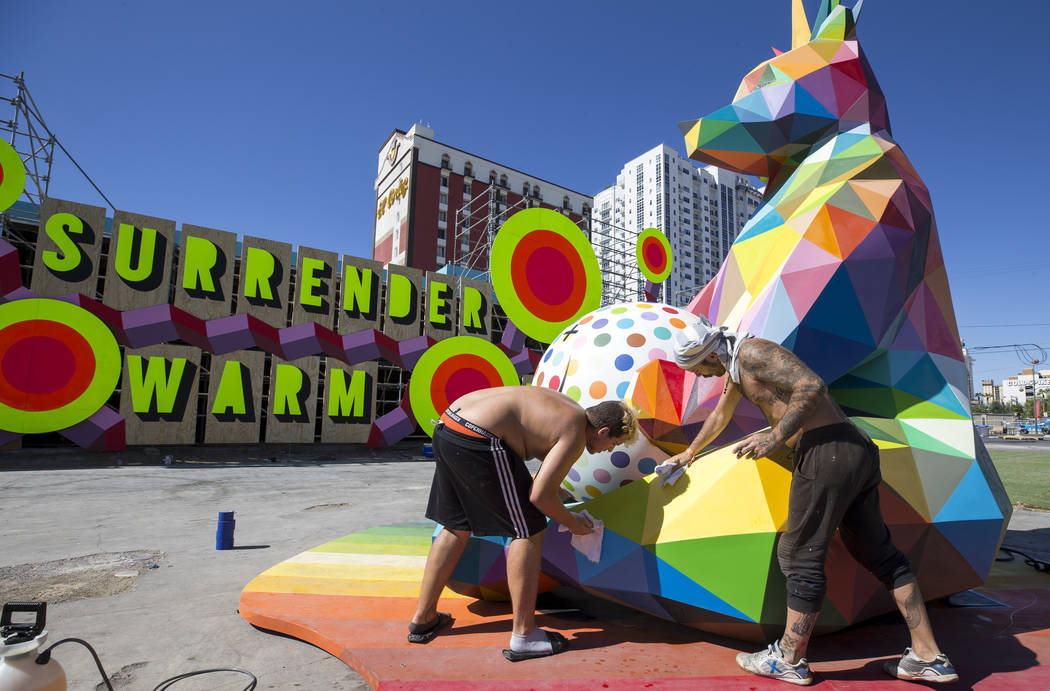 Marcos Martinez, left, and Pablo Hattori, assistants to Spanish street artist Okuda San Miguel, clean up a sculpture created by Okuda in preparation for the Life is Beautiful festival in downtown  ...