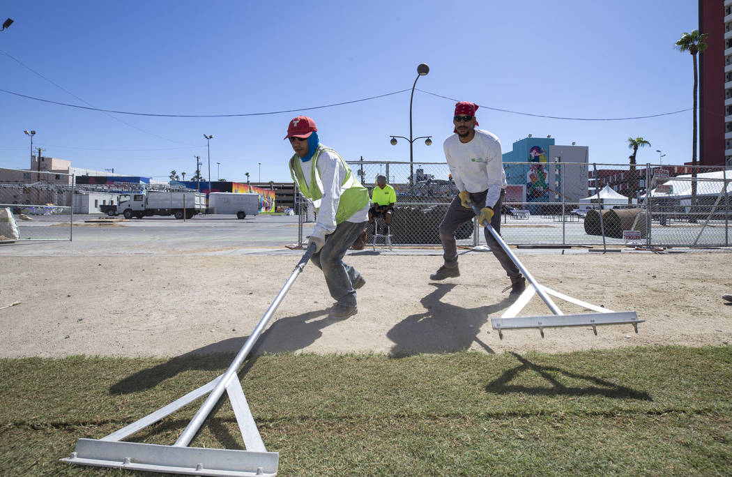 Landscapers Amilcar Mejia, left, and Shaun Richardson, of Newtex Landscape Inc., lay down sod in front of the Huntrdige stage in preparation for the Life is Beautiful festival in downtown Las Vega ...