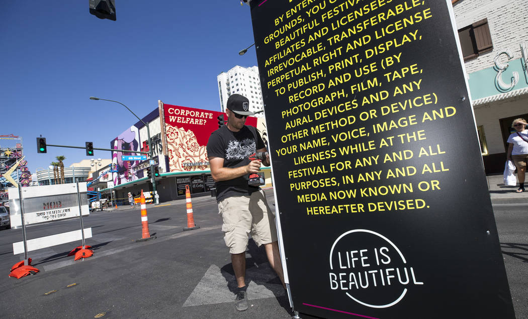 Sign installer Mark Fox, of Deluxe Designs, builds an informational sign near the intersection of 6th Street and East Fremont Street in preparation for the Life is Beautiful festival in downtown L ...
